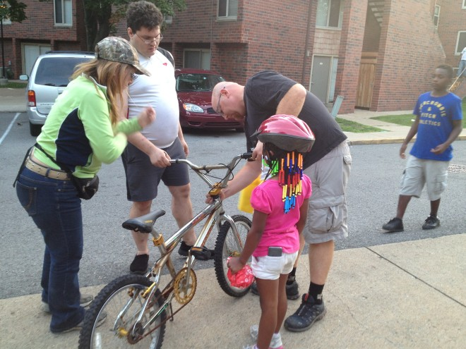 Volunteers fixed bikes and fitted helmets to keep kids safe.